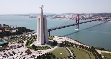 largest city : Aerial view  ovet the April of 25 bridge in Lisbon, crossing the Tagus River and Statue of Jesus , Portugal