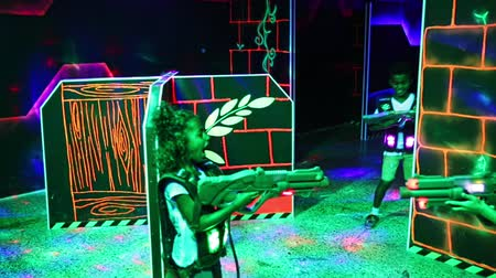 painless : Joyful teens aiming laser guns at other players during lasertag game in dark room