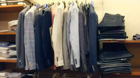 sala de exposição : Variety of different suit jackets exposed on clothing rack in men clothes shop