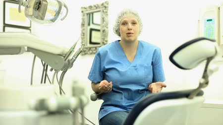 competence : Dentist woman near dental chair, welcoming patient to office