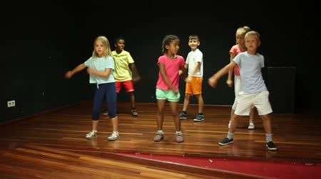 taniec towarzyski : Positive children studying modern style dance  in class indoors