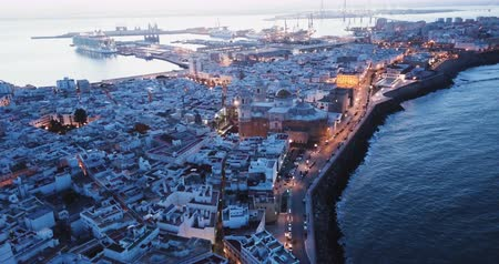 impressive skyline : Panoramic view of illuminated Cadiz port city with medieval Cathedral at dawn, Spain