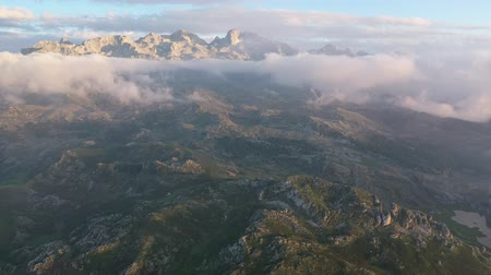 foothills : Unique landscape of Picos de Europa with rocky mountain ranges in thick clouds during sundown, Spain