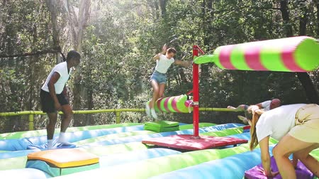 valente : Funny adult friends are jumping on an inflatable trampoline