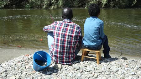 mulatte : Back portrait of afro man and little boy sitting near river and holding fishing rod Filmati Stock
