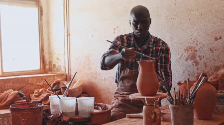 potter wheel : Professional African American male potter painting ceramic pot in pottery workshop