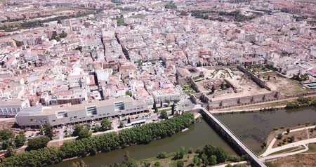 emerita : Aerial panoramic view of modern Merida cityscape on banks of Guadiana River with ancient pedestrian Roman Bridge, Spain