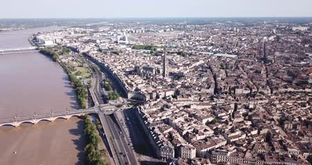 michael : Aerial view of Bordeaux cityscape on banks of Garonne river overlooking Gothic spire of Basilica of St. Michael, France Stock Footage