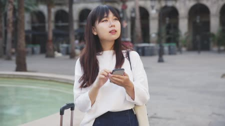 juni : Tourist chinese girl using her phone in the town on vacation Stockvideo