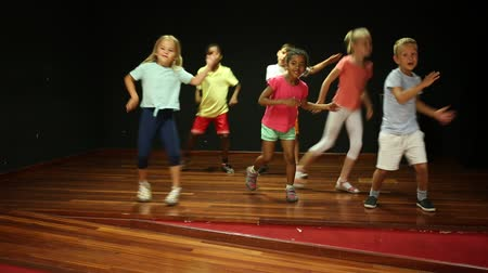 dez : Positive children studying modern style dance in class indoors