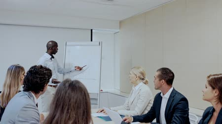 bancário : Afro male office worker presenting strategy to colleagues in modern office