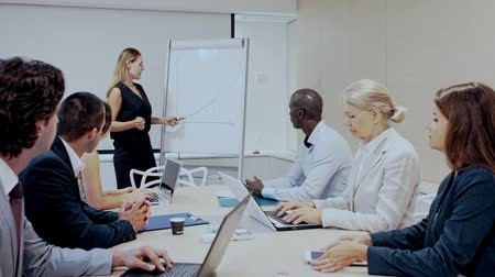 desenvolver : Young successful businesswoman sharing business ideas with colleagues in meeting room. Concept of teamwork