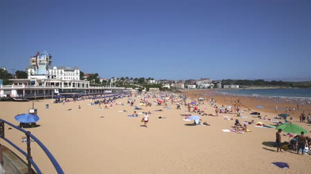 baleár : SANTANDER, SPAIN - JULY 14, 2019: View of city beach of Santander with people lying and walking on sand Stock mozgókép