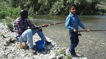 mulatte : Portrait of cheerful afro man and his little son fishing with rods on river Filmati Stock