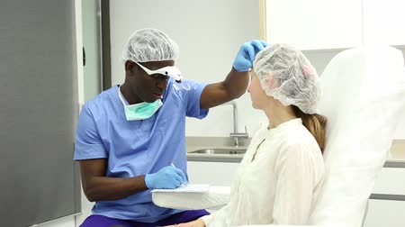 mezoterapia : Cosmetician male examining patient face skin before aesthetic procedure and writing to workbook in medical  office