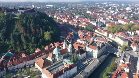 fortificado : Aerial view of Slovenian town of Ljubljana overlooking fortified castle on hill and Roman Catholic Cathedral in morning sunlight