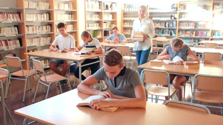 scolari : Teenage pupils sitting at table and studying, teacher in classroom