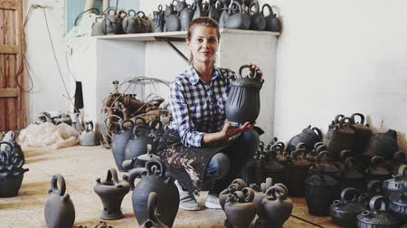 ón : Woman chooses pots clay pots in store warehouse