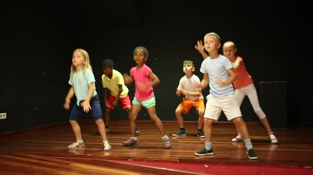 devět : Cheerful little boys and beautiful girls having dancing class  in studio