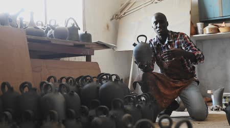 itens : Friendly young salesman of pottery store offering traditional African handmade ceramic goods