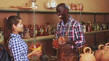cortes : Smiling African potter offering handmade earthenware to young female client in modern ceramics workshop