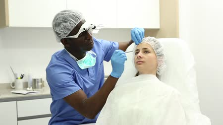 otuzlu yıllar : Cosmetologist man in mask preparing  woman client for mesotherapy  procedure  in medical  office Stok Video