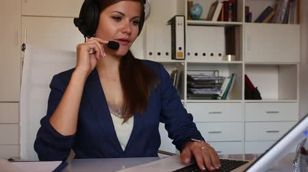 dispatcher : Smiling young female operator talking with customer using headset at company office