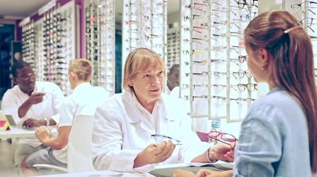 optyk : Smiling elderly woman optician offering stylish glasses in modern optical store