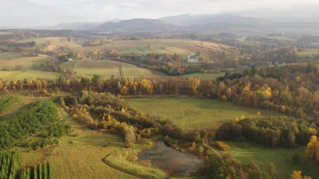 склон холма : Panoramic autumn view of church, hills and fields near Boboszow, Poland