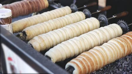 bread stick : Traditional cooking of Czech trdelnik on street market - yeast rolled dough wrapping around stick and baking on grill