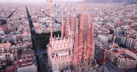 stationary : BARCELONA, SPAIN- JUNE 13, 2019: Aerial view of Sagrada Familia on background of Eixample district cityscape at twilight