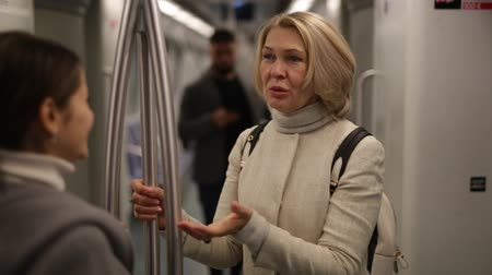 cortes : Portrait of mature woman talking friendly with her fellow traveler in modern subway car