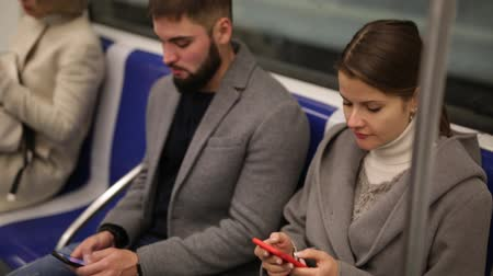 rendes : Man and woman using phone inside subway