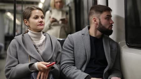 cortes : Positive bearded guy enjoying friendly conversation with young woman while traveling on subway train