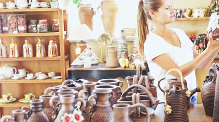 kamenina : Positive young woman looking for handmade ceramic products in craft pottery shop