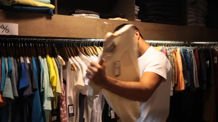 verkoopstyling : Positive man looking for new casual clothes at garments shop