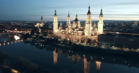 Scenic twilight view from drone of illuminated Basilica of Our Lady of Pillar on bank of Ebro river in Spanish city of Zaragoza