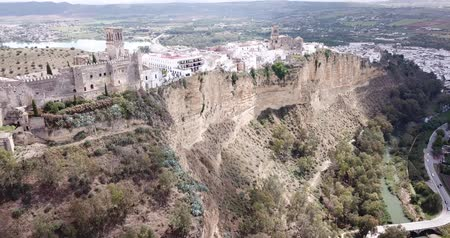 Picturesque landscape with old Spanish town of Arcos de la Frontera atop sandstone ridge