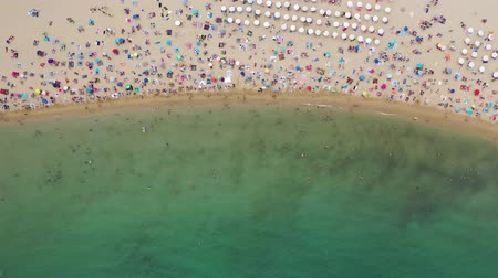 Picturesque overview of ocean shoreline with colored umbrellas of vacationers on sandy beach