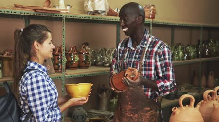 kamenina : Smiling African craftsman offering to young woman for sale popular authentic stoneware and ceramic products