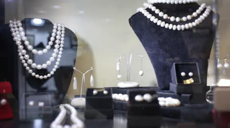 cenný : Variety of necklaces, bracelets and earrings made of white and black pearls on mannequins in jewelry store window