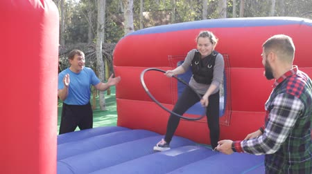 çabaları : Cheerful woman playing tug of war with hoop on inflatable arena in outdoor amusement park Stok Video