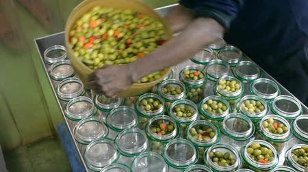 agrarian : Worker prepares glass jars and olives for canning