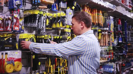 locksmith : Confident man is choosing locksmith tools in tools store