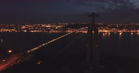 süspansiyon : Morning aerial view from Almada of Sanctuary of Christ King and 25 de Abril Bridge against backdrop of lighted Lisbon, Portugal Stok Video