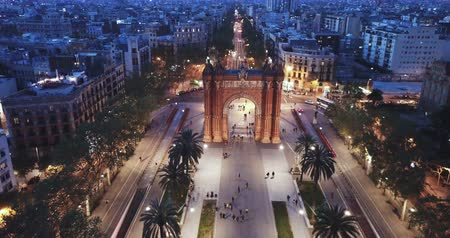 reddish : Aerial view of iconic landmark of Barcelona - Triumphal Arch (Arco de Triunfo) on central avenue at twilight, Spain