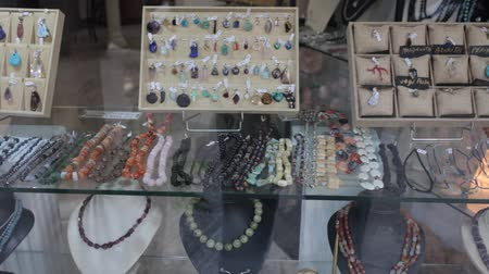 šperk : Collection of natural gemstone beads displayed for sale on shelf of jewelry boutique