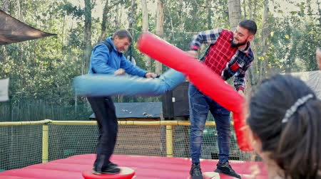 Happy male friends fighting by big stuffed boxing gloves at outdoor amusement playground Stock mozgókép