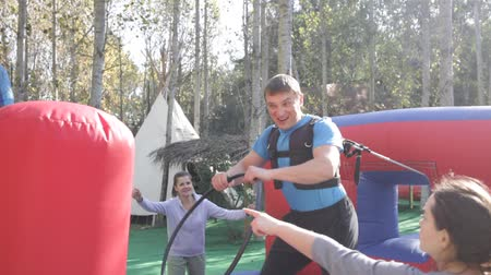 Emotional man tied with rope to his friend competing to collect hoops on inflatable ring Stock mozgókép