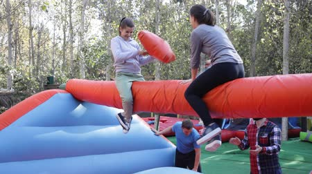 Female friends having funny wrestling by pillows on inflatable beam in outdoor amusement park Stock mozgókép